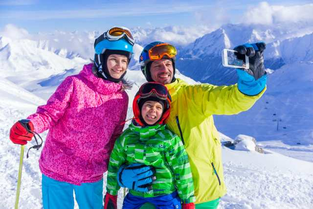 Skiing, winter fun - happy family taking picture at the ski slope
